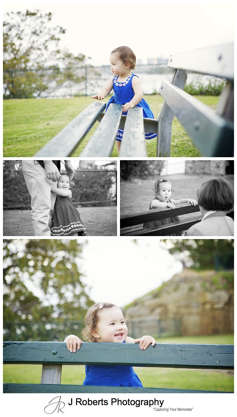 Little girl playing peek a boo with park bench - sydney family portrait photographer